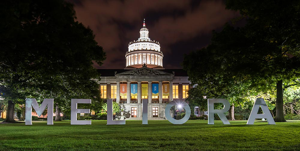 giant MELIORA letters lit up against Rush Rhees Library at night