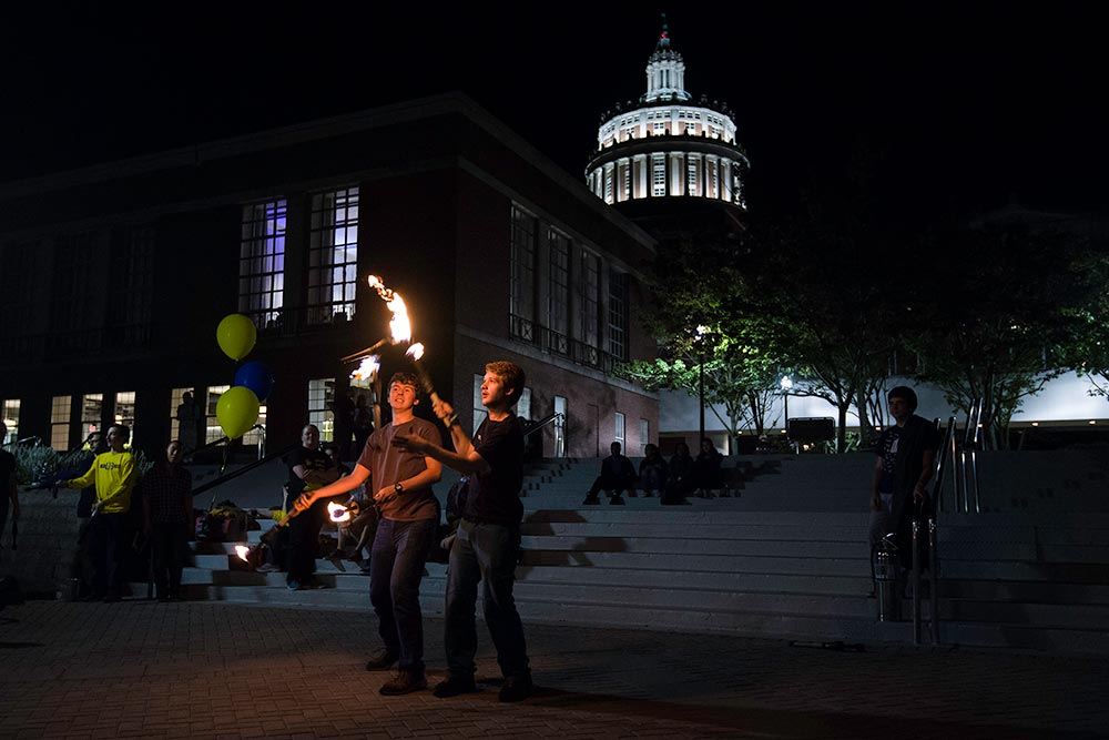 juggling fire in front of Rush Rhees Library