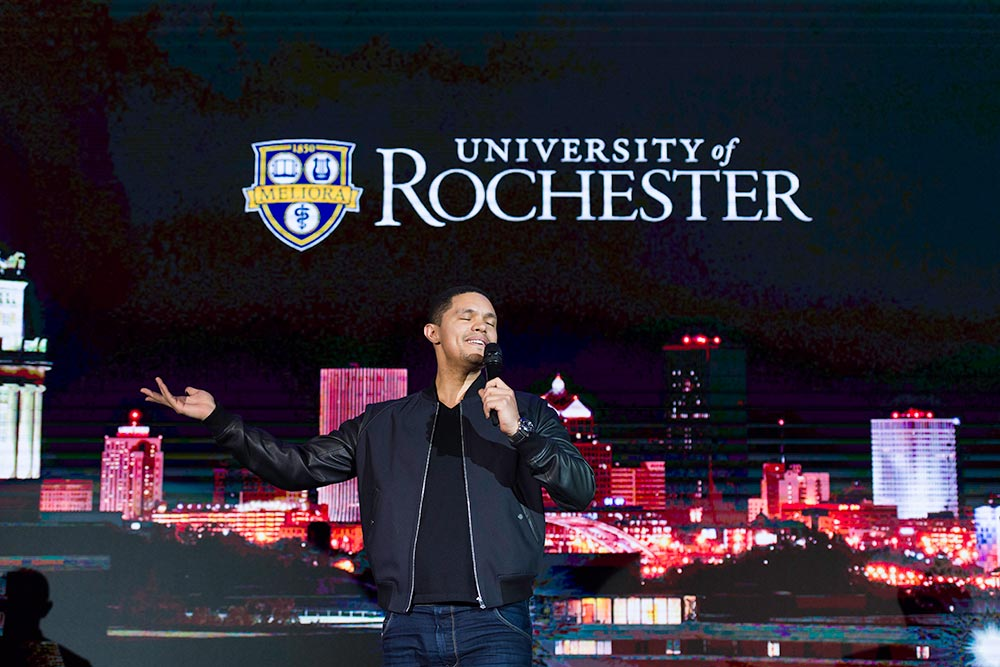 Trevor Noah on stage in front of a University of Rochester logo.