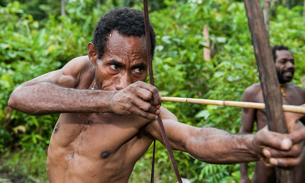 shirtless man in New Guinea shooting a bow and arrow