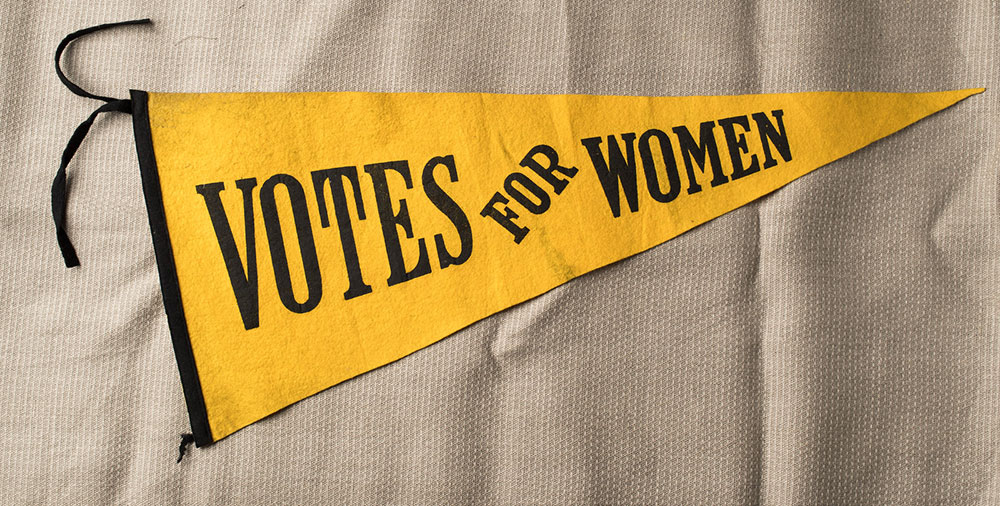 yellow penant reads VOTES FOR WOMEN