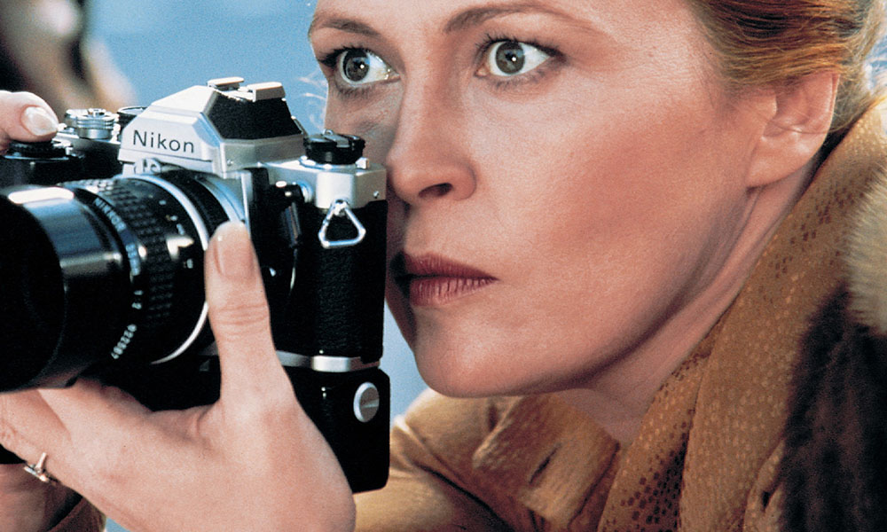 Faye Dunaway focuses a camera.