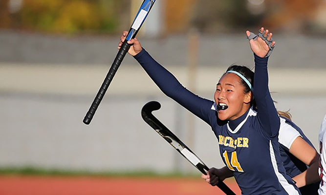 field hockey player with hands raised in celebration