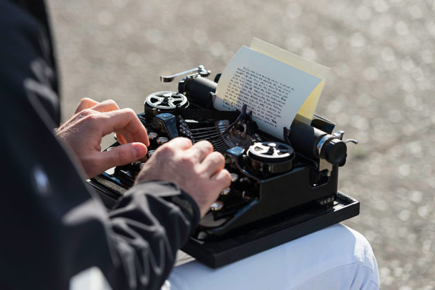 close-up of hands typing on old typewriter