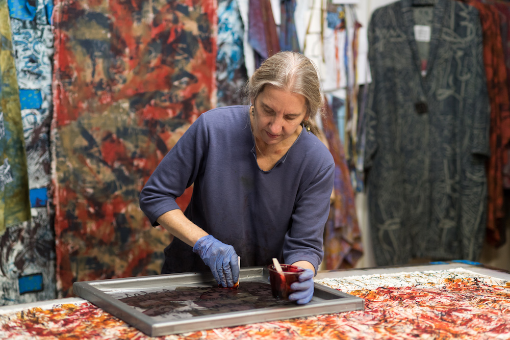 woman painting a screen on top of a table