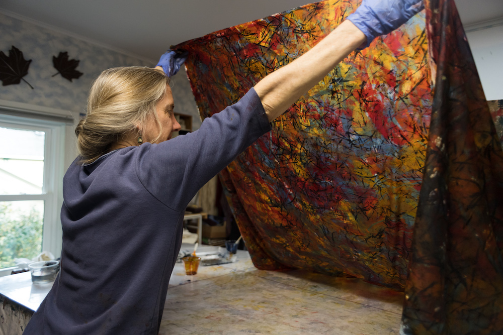 artist holds up dyed fabric