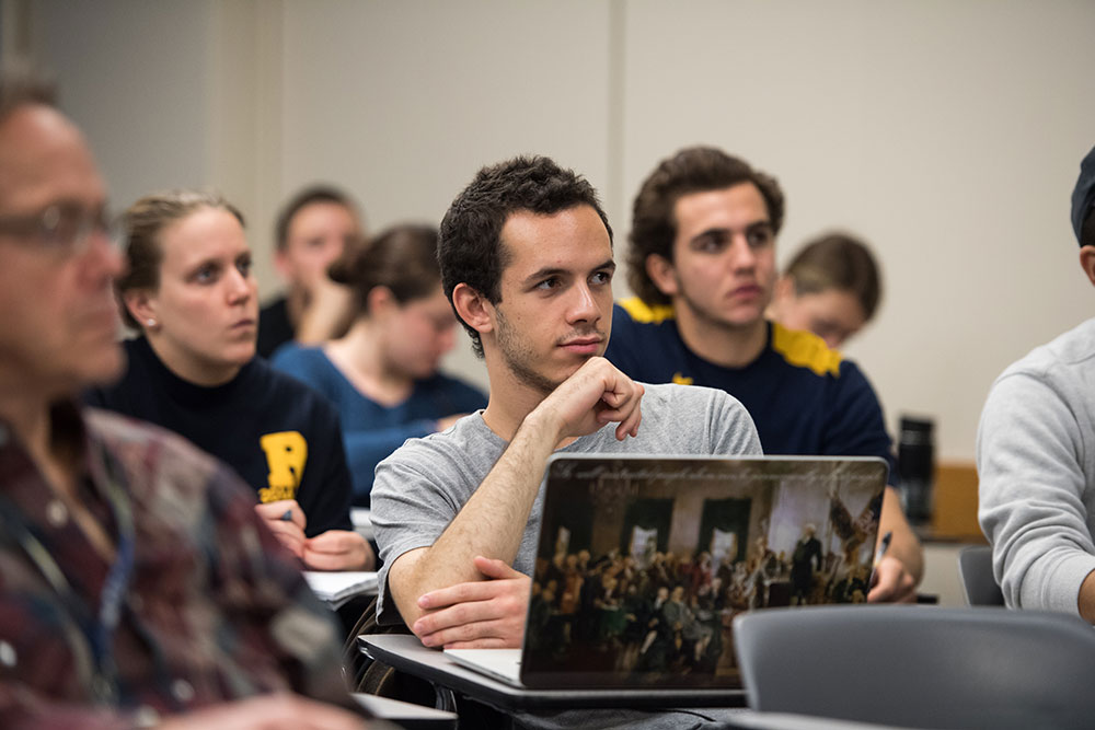 student with laptop decorated with painting of the Founding Fathers