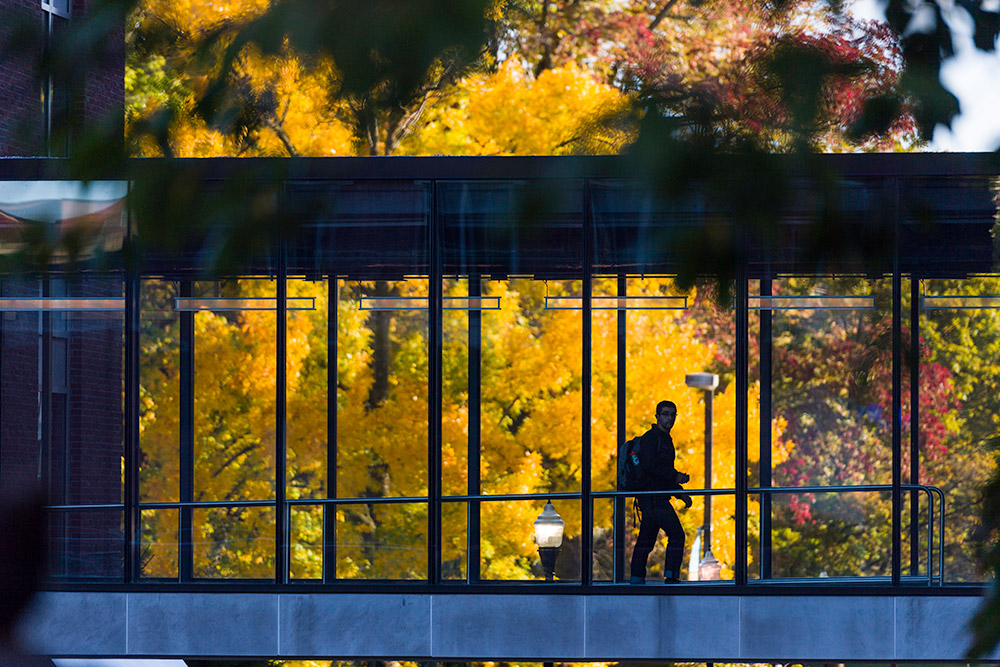 student walking across Douglass bridge with fall leaves behind