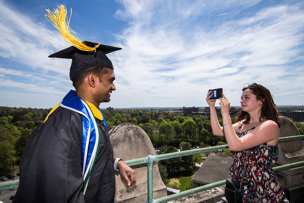 graduate in cap and gown gets picture taken on top of library tower