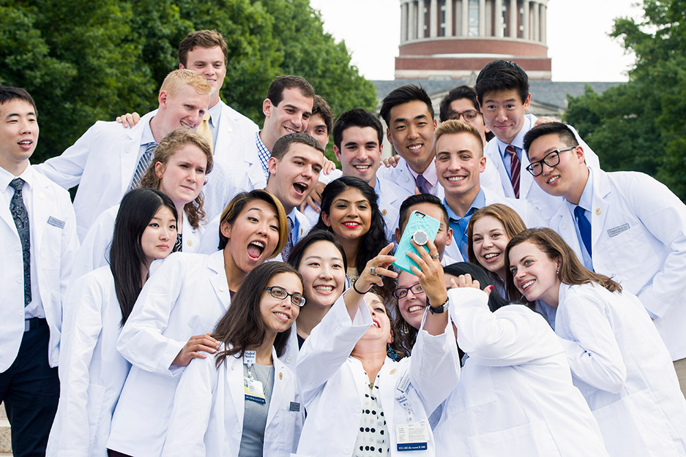 large group of medical students in white coats taking selfies