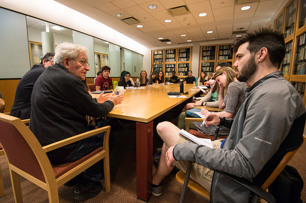 Noam Chomsky sitting at conference table with students