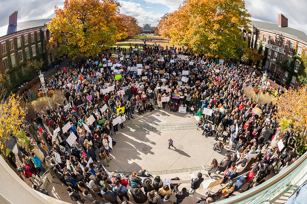 large group of demonstrators standing in a circle on the quad