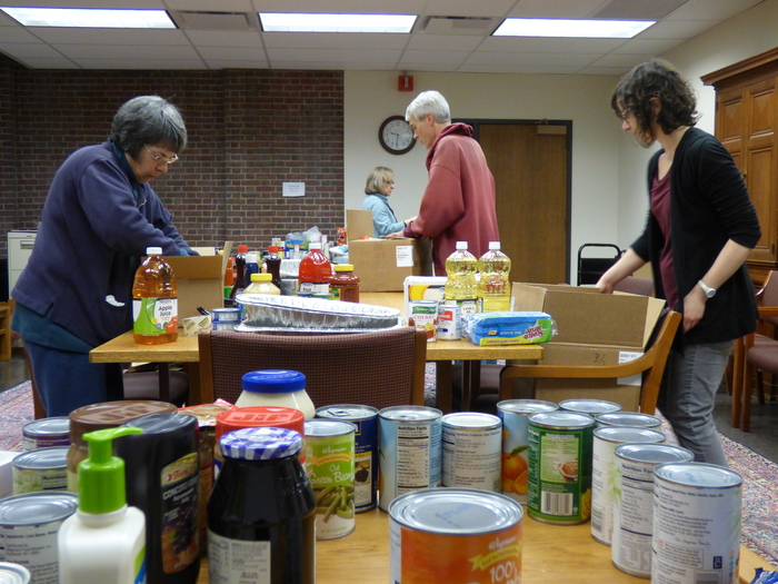 River Campus Libraries staff members (from left to right) Patricia Curran, Jennifer Bowen, David Hull, and Esther Arnold pack food donations to be delivered to Baden Street Settlement families for Thanksgiving.