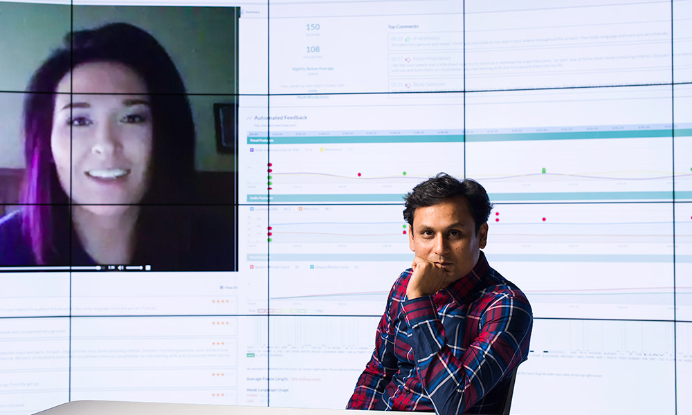 researchers sits in front of a large screen that contains the image for a human face, speaking