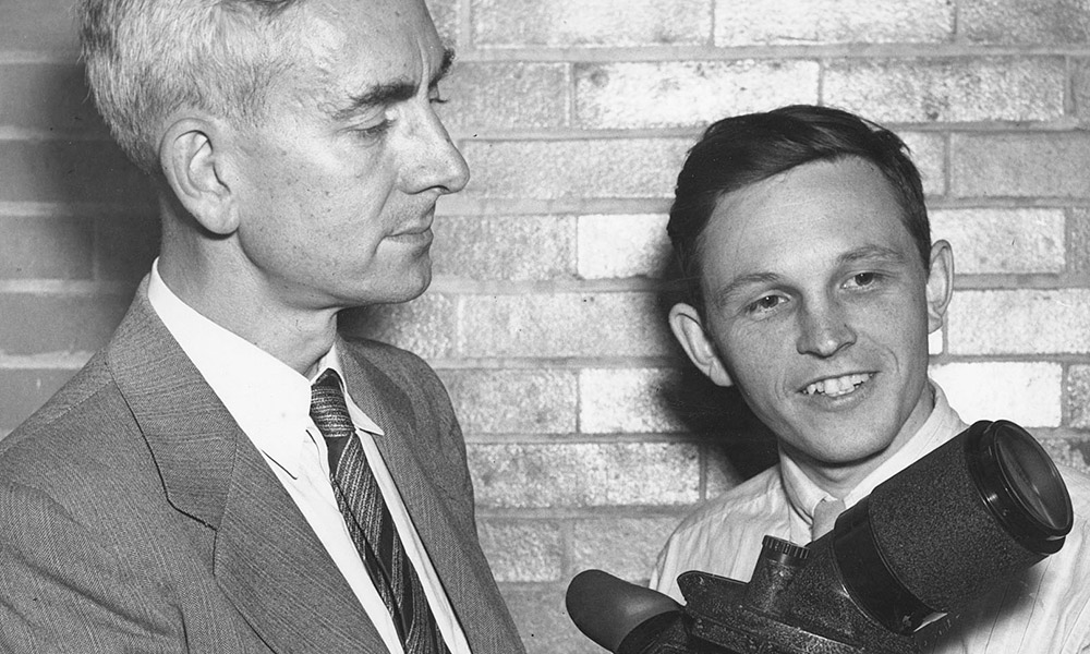historic image of two men holding an optica device called an Icaroscope, which looks like a large, camera lens