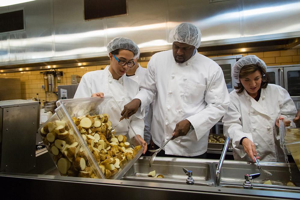 three people preparing meals