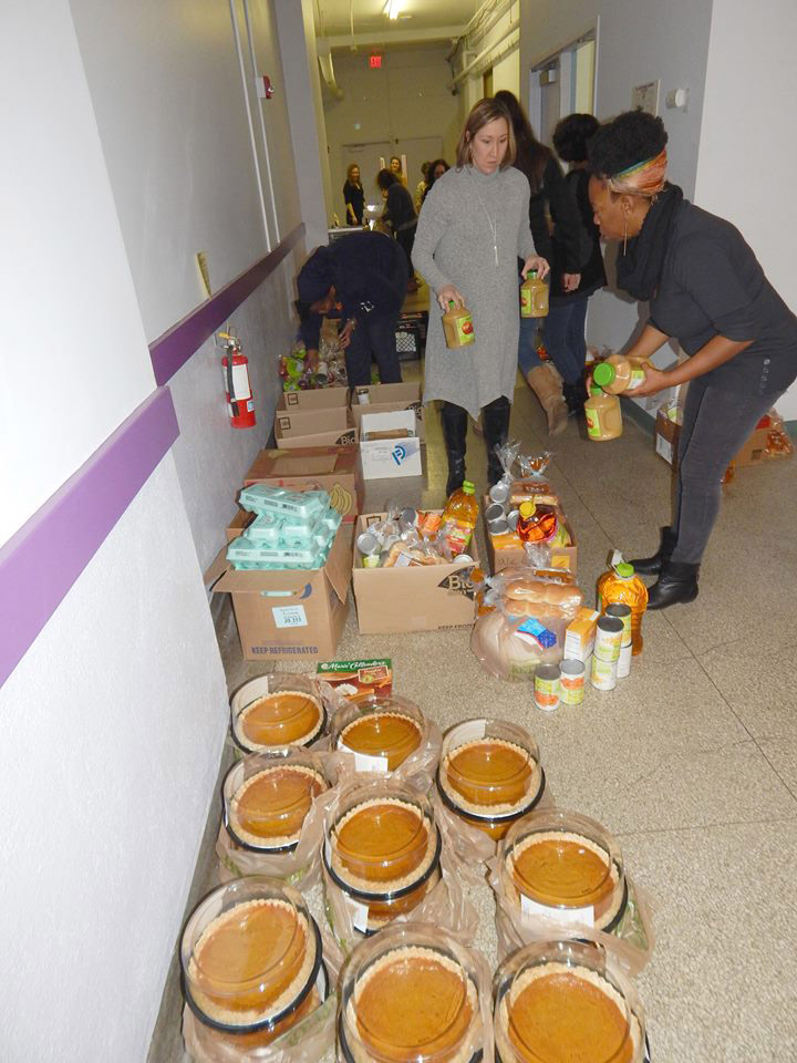 two people organizing pumpkin pies and other food items