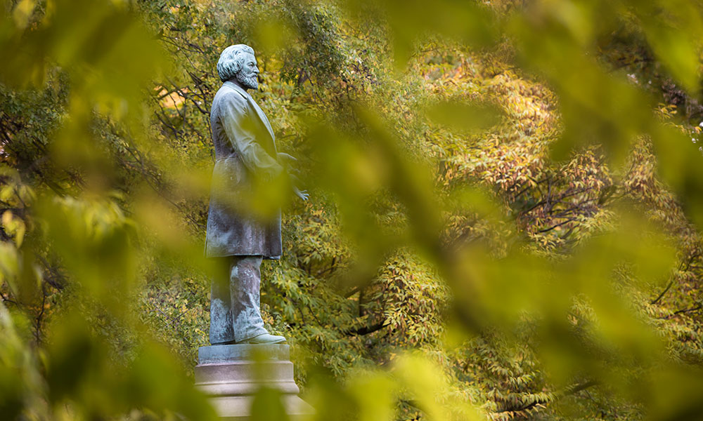 statue of Frederick Douglass surrounded by fall trees