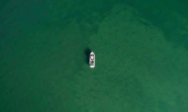 aerial shot of boat on a large body of water