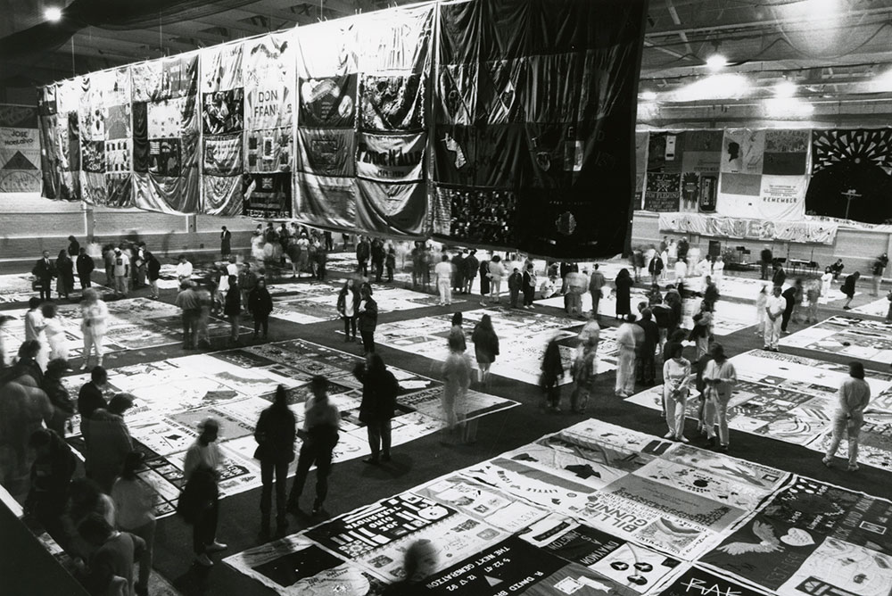 archival photo of AIDS quilt laid out with people walking around it