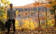 Ulrik Soderstrom standing in Letchworth State Park with fall foliage all around.