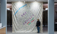 woman stands next to 12-foot high panel signed with many names