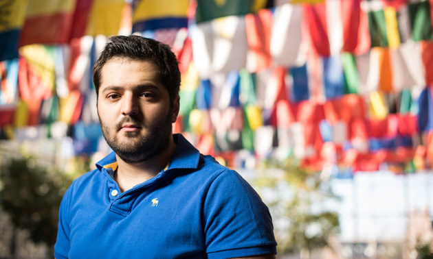 Omar Soufan stands in front on display of world flags