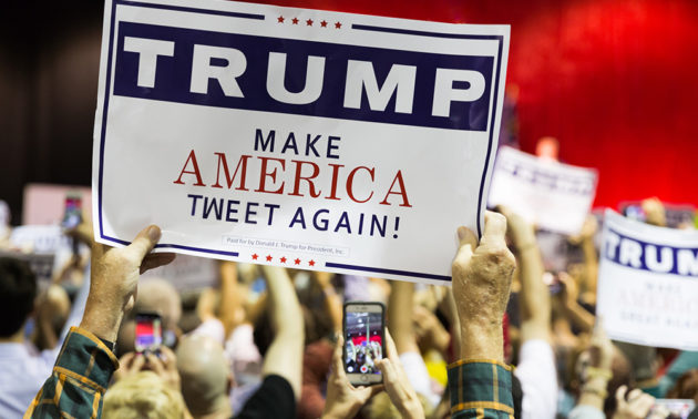 man in crowd holds sign edited to read MAKE AMERICA TWEET AGAIN