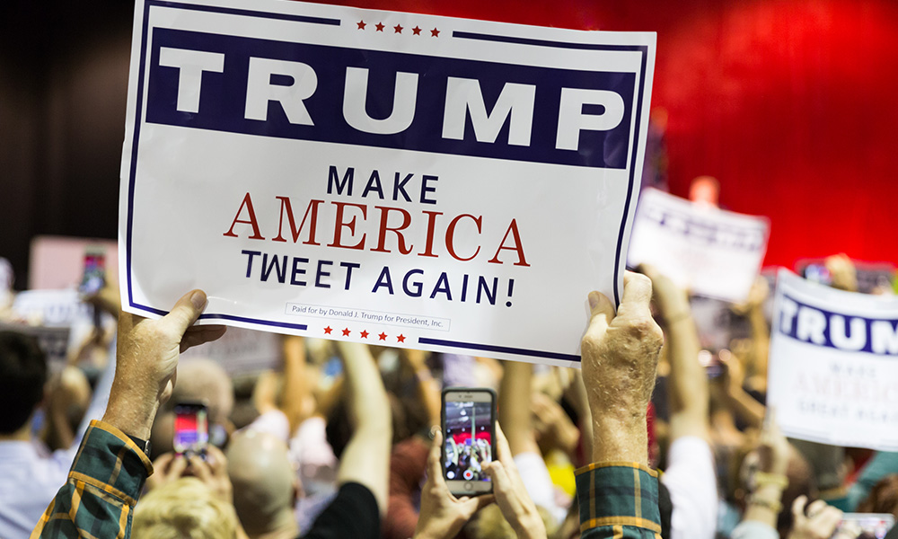 man in crowd holds Trump sign edited to read MAKE AMERICA TWEET AGAIN/
