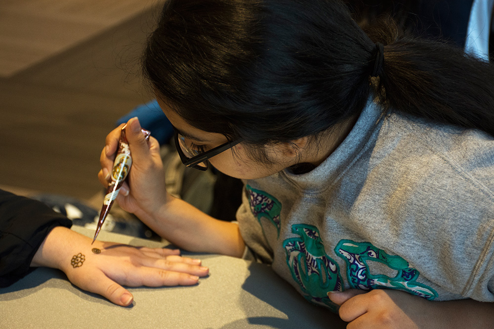 student painting a henna tattoo on someone's hand
