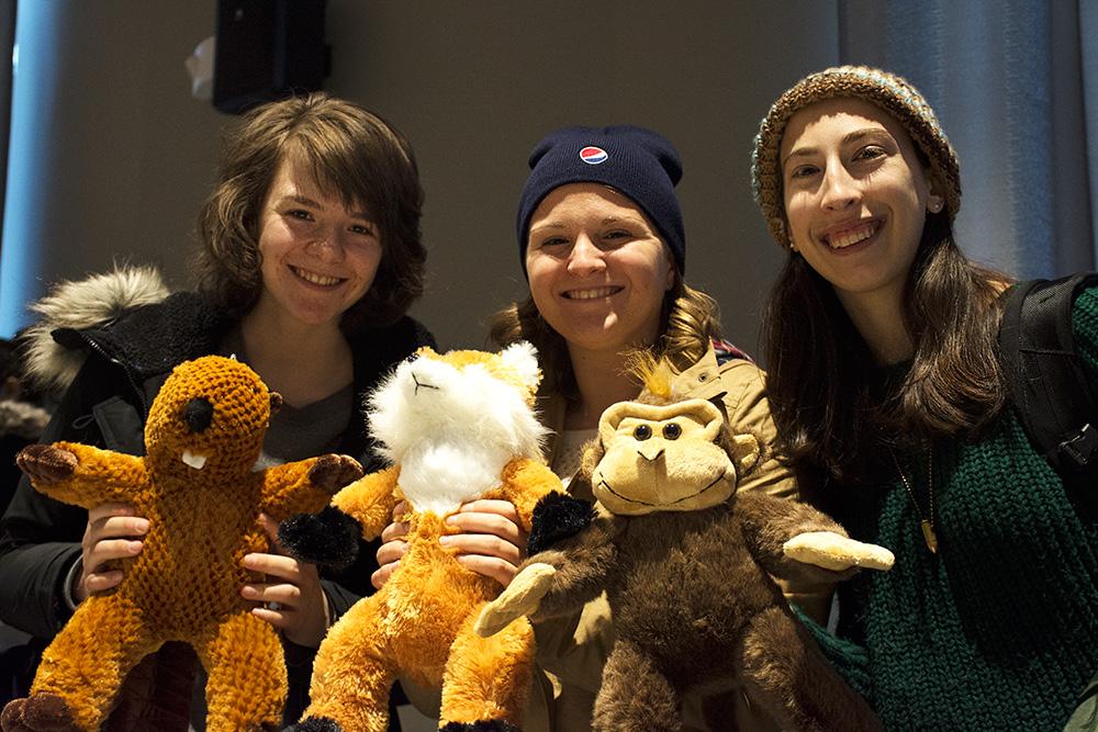three students holding stuffed animals