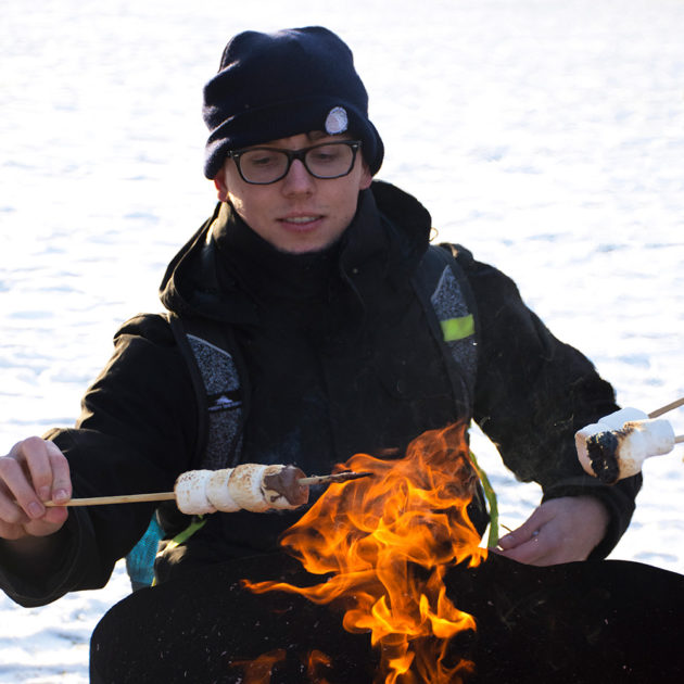 student toasting marshmallows over a fire