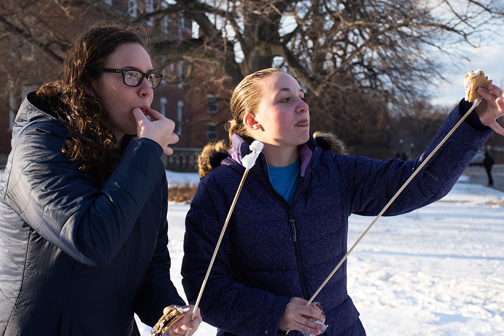 two students eating smores.