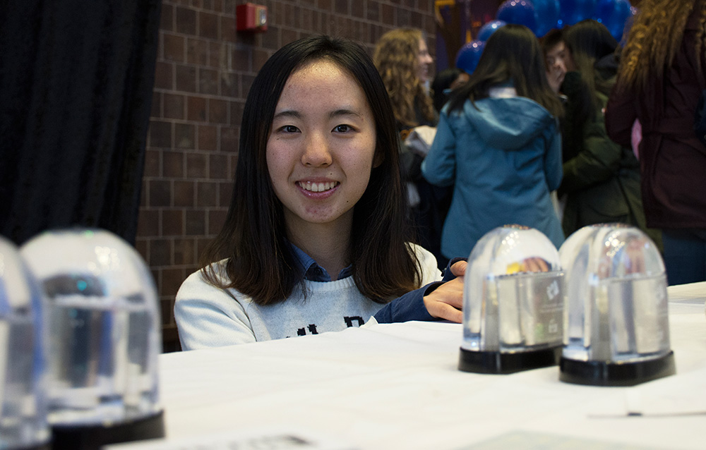 student poses with snowglobes