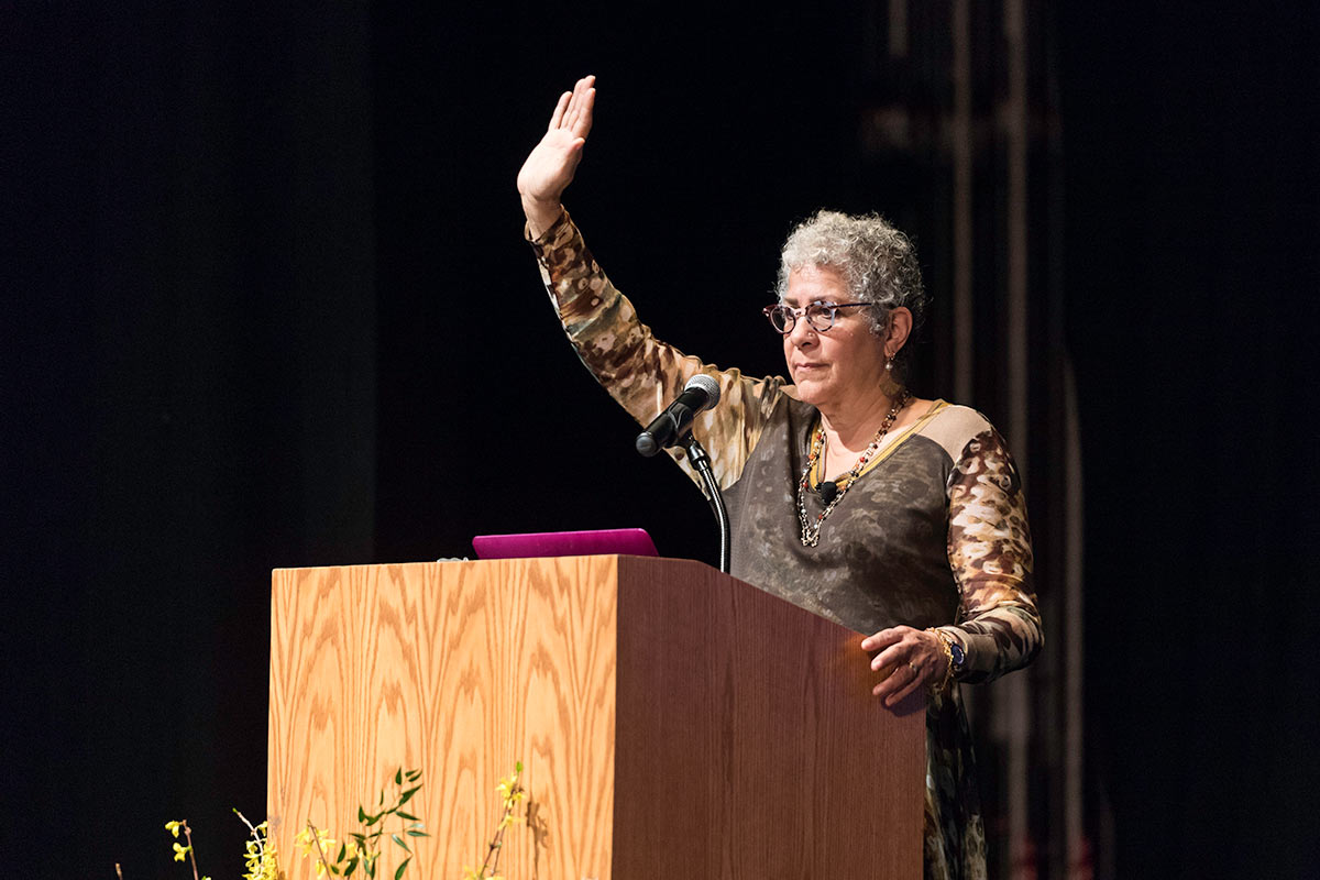 woman at podium with her arm raised