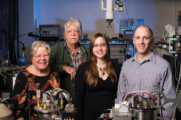 group of four scientists pose for a photo in their lab