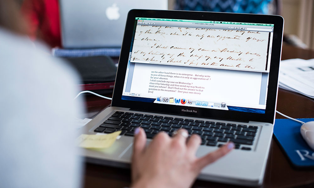woman at laptop, screen showing handwritten document with typed transcript
