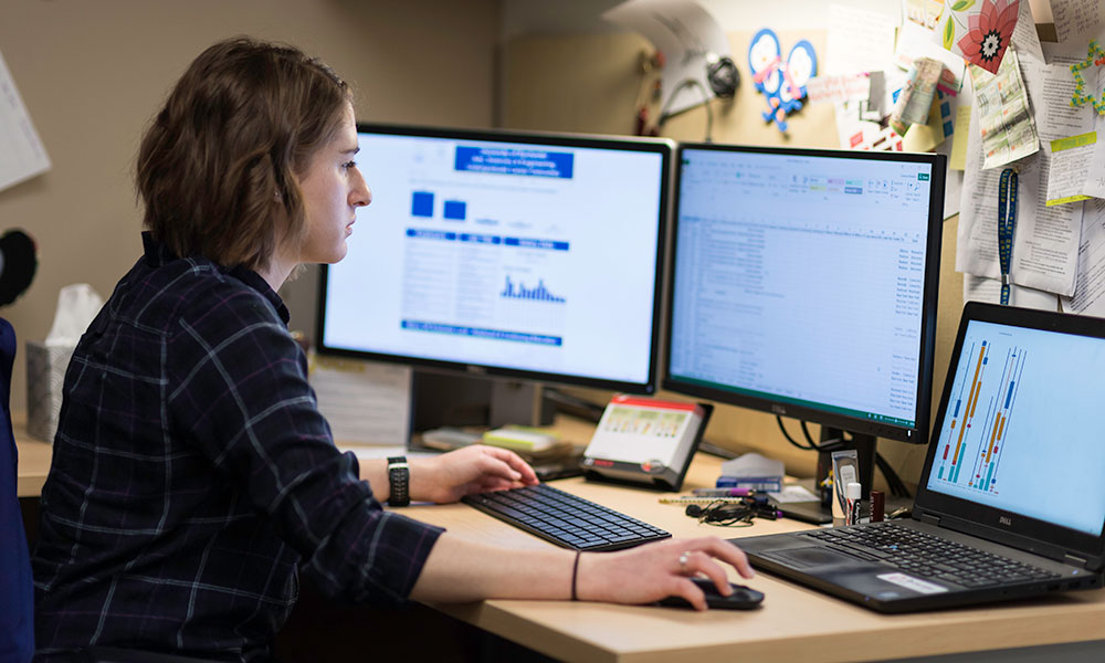 woman works at computer with multiple monitors displaying data