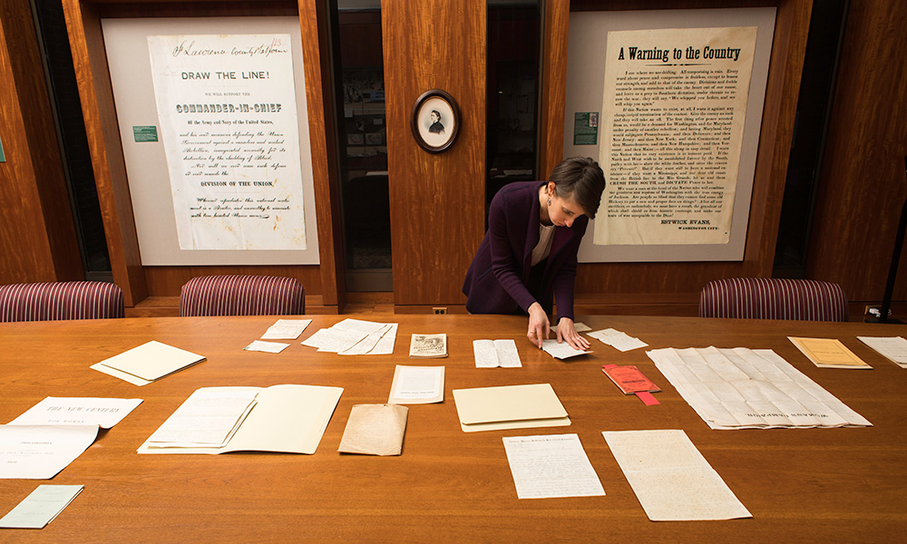 librarian with a large table covered in letters