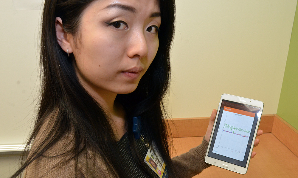 woman holds an iPad device showing data charts