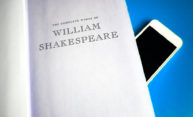 book of William Shakespeare with smartphone peaking out behind it