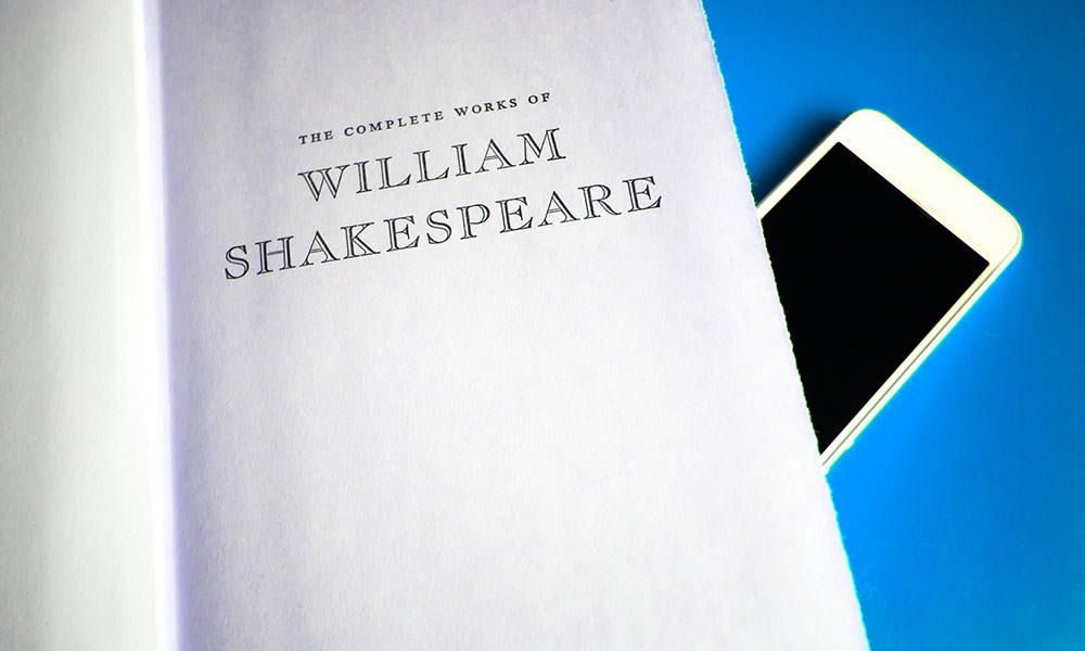 cell phone sitting on a book of William Shakespeare