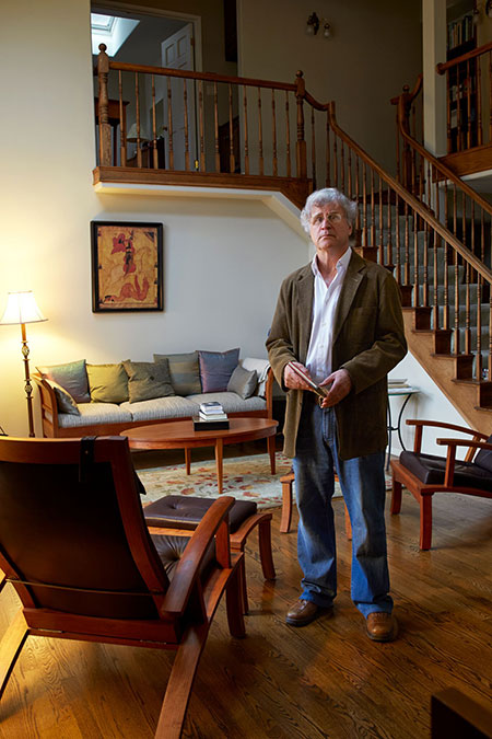 man standing in library in his home