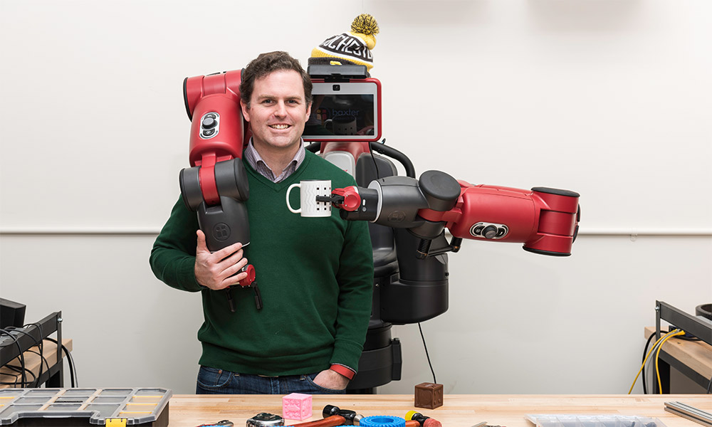 man with robot holding a coffee cup in front of him