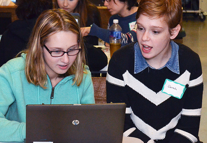 student helping another student at the laptop