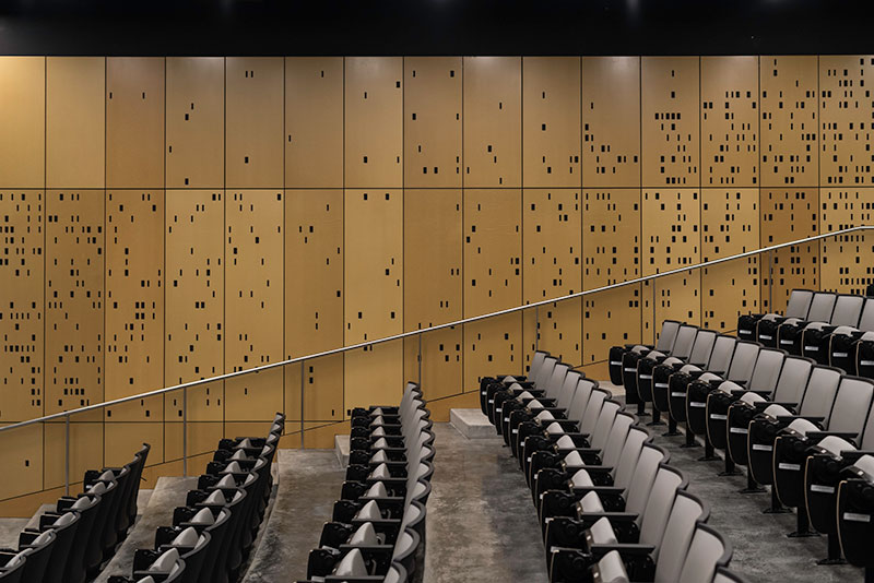 auditorium with walls made to look like computer punch cards
