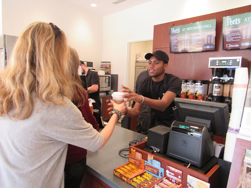 coffee shop with worker handing coffee to a customer
