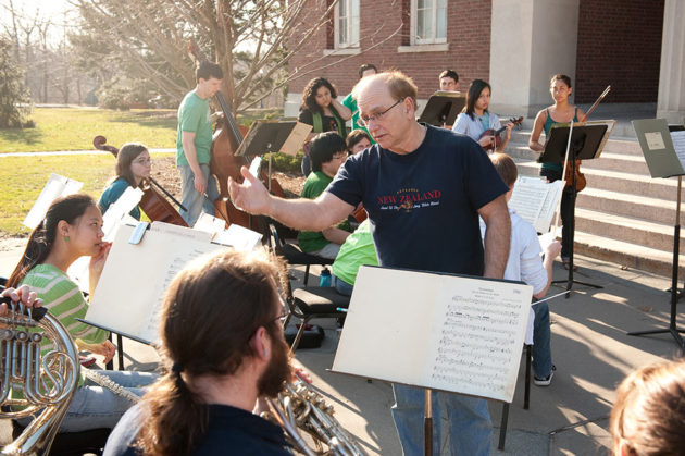 Man teaching orchestra class outside Rush Rhees library