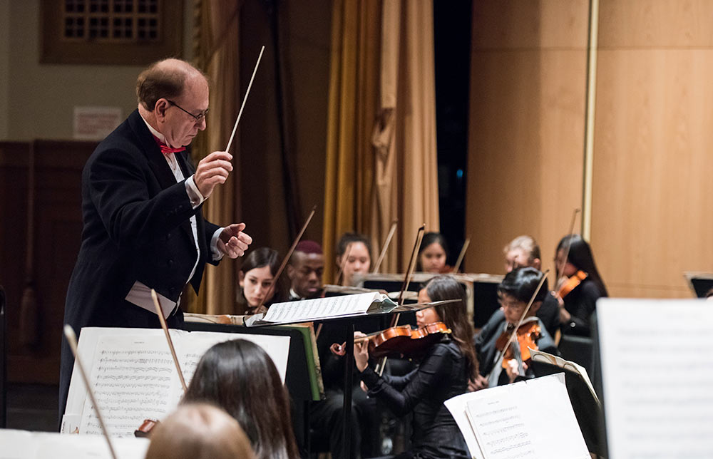 man in coat and tails conducting an orchestra