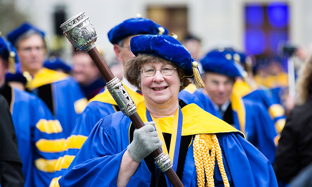 administrator in academic regalia carrying the mace at the head of the commencement processional